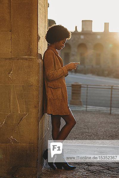Junge Frau mit Afro-Haaren  die ein Smartphone benutzt und sich gegen eine Steinmauer lehnt  Florenz  Toskana  Italien