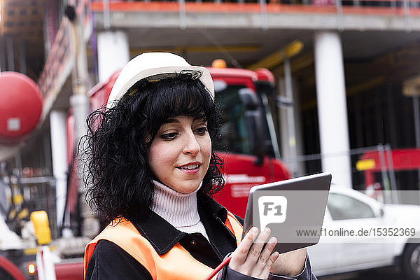 Female surveyor looking at digital tablet on construction site