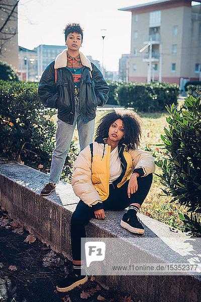 Zwei coole junge Freundinnen auf Stadtmauer  Porträt
