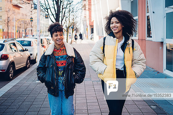 Zwei coole junge Frauen schlendern auf dem städtischen Bürgersteig