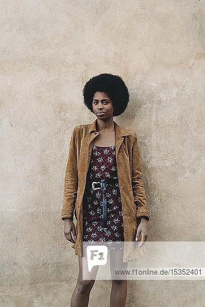 Junge Frau mit Afro-Haaren wartet an Steinmauer
