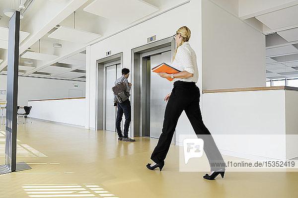Geschäftsfrau und Geschäftsmann im Bürokorridor
