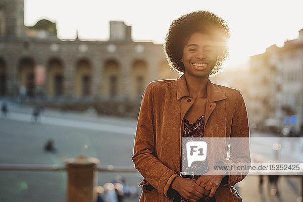 Junge Frau mit afrofarbenen Haaren  die am Geländer lehnt  Florenz  Toskana  Italien