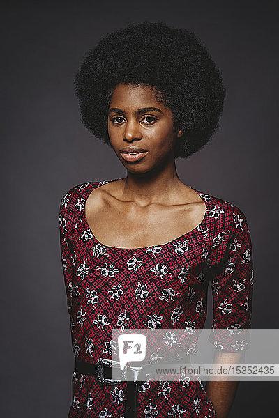 Junge Frau mit afrofarbenen Haaren vor grauem Hintergrund