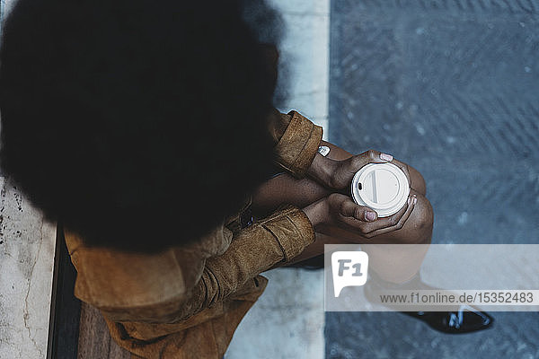 Frau mit Afro-Haaren umklammert Heißgetränk