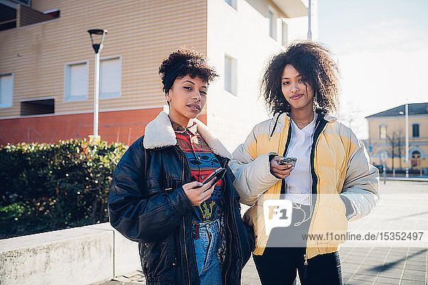 Two cool young female friends with smartphones on urban sidewalk  portrait