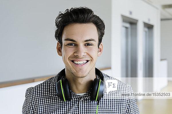 Businessman with headphones in office corridor