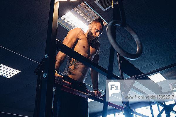 Junger Mann trainiert im Fitnessstudio,  macht Liegestütze an der Stange