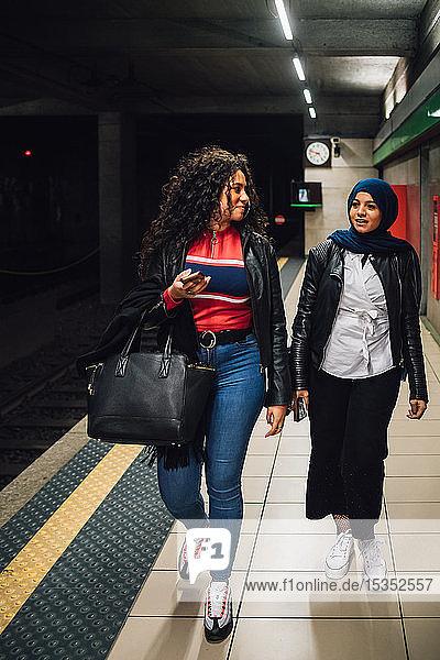 Junge Frau im Hidschab mit Freundin auf U-Bahn-Bahnsteig