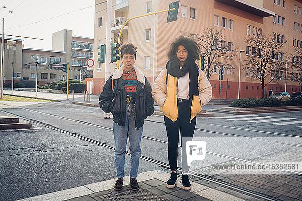 Zwei coole junge Frauen stehen an der städtischen Straßenbahnlinie