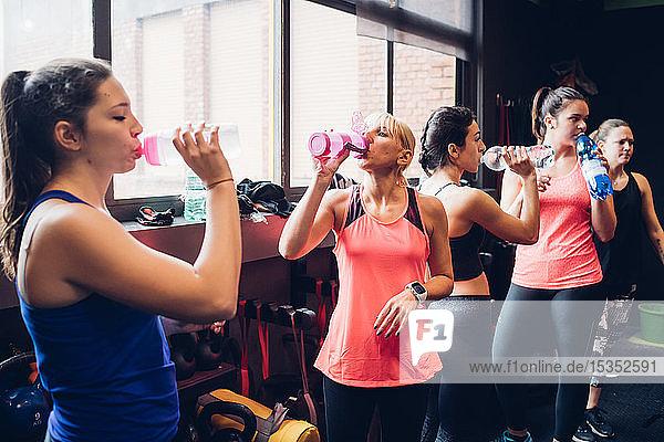 Group of women training in gym  taking a break drinking bottled water