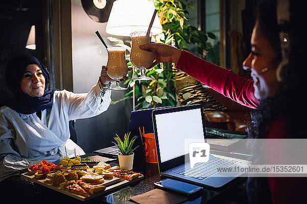 Young woman in hijab raising a glass with friend in cafe