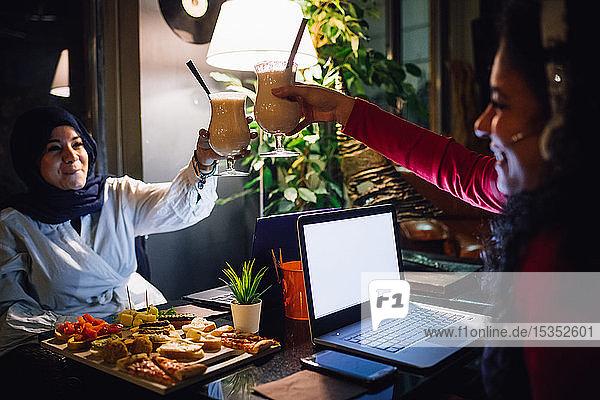 Junge Frau im Hidschab hebt mit Freundin im Café ein Glas