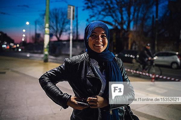 Junge Frau im Hidschab auf dem nächtlichen Bürgersteig der Stadt  Porträt