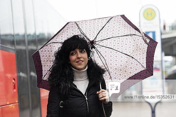 Mittlere erwachsene Frau mit Regenschirm an der städtischen Straßenbahnhaltestelle