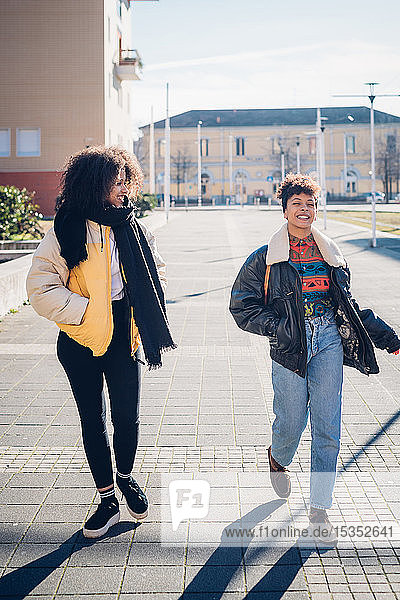 Two cool young female friends walking and talking on urban sidewalk