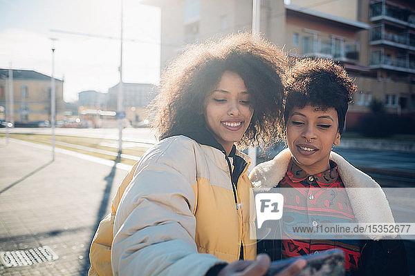 Zwei coole junge Freundinnen mit Smartphone-Selfie auf dem städtischen Bürgersteig