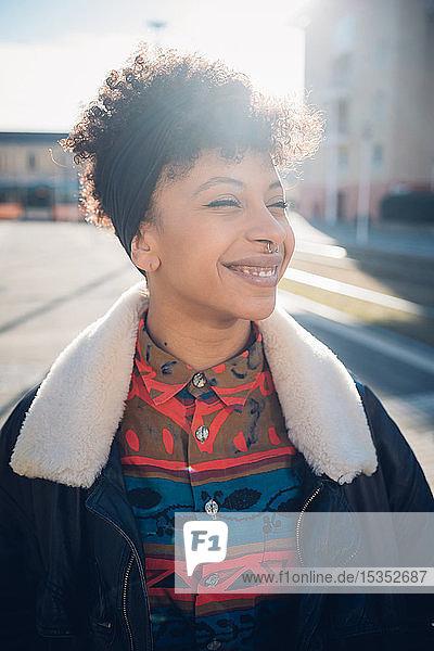 Kühle junge Frau mit Nasenpiercing auf dem sonnenbeschienenen städtischen Bürgersteig  Porträt