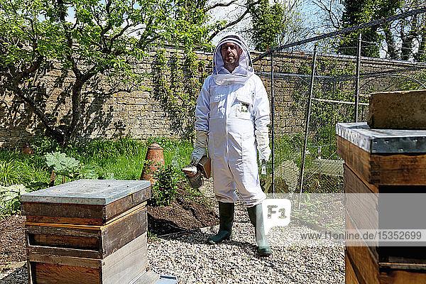 Male beekeeper carrying bee smoker in walled garden  portrait