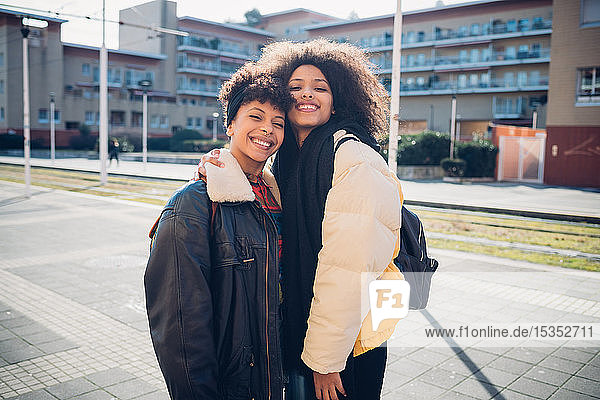 Zwei junge Frauen posieren auf dem städtischen Bürgersteig  Porträt