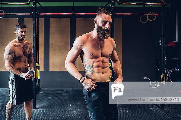 Young tattooed men training in gym  taking a break