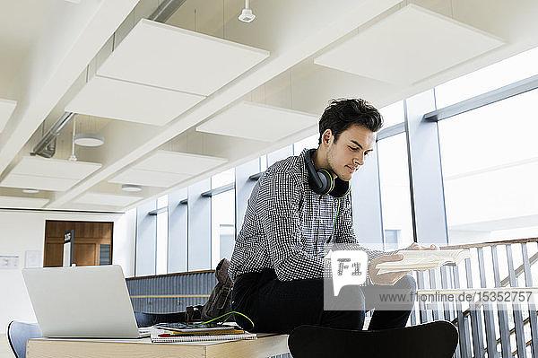 Geschäftsmann mit Kopfhörer liest Buch im Büro