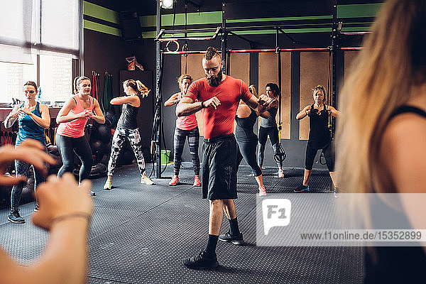 Group of women training in gym with male trainer,  twisting