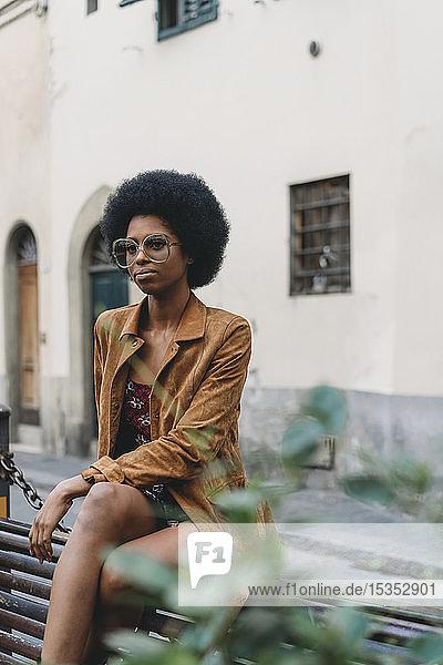 Junge Frau mit Afro-Haaren wartet vor dem Gebäude