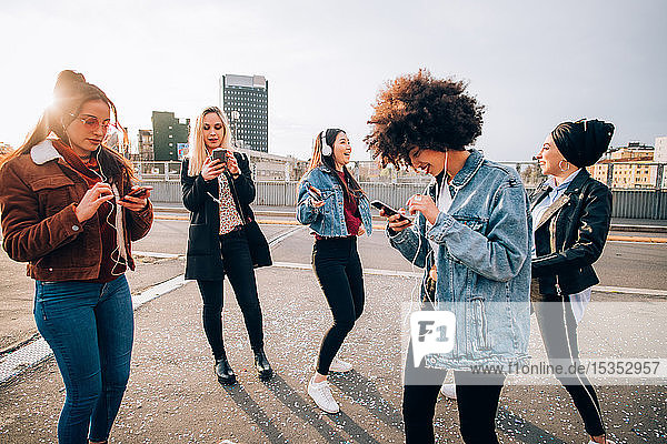 Friends dancing in street to smartphone music  Milan  Italy