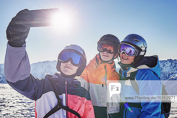 Skiers  mother with teenage son and daughter taking selfie on snow covered mountain top  Alpe-d'Huez  Rhone-Alpes  France