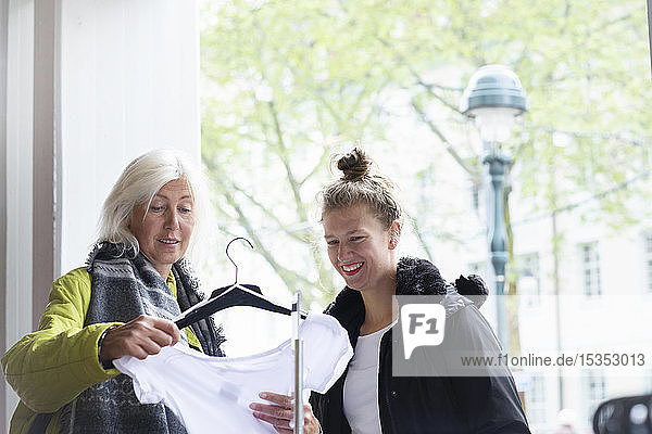 Mature woman and daughter looking at t-shirt in shop