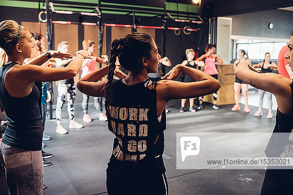 Group of women training in gym  with arms raised