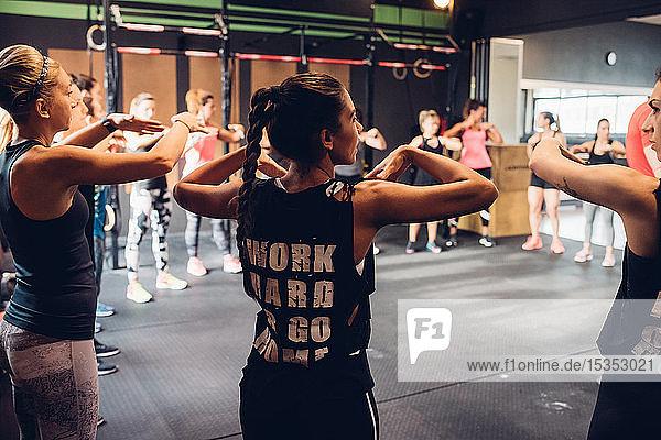 Gruppe von Frauen trainiert im Fitnessstudio  mit erhobenen Armen