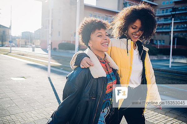 Two cool young female friends strolling on sunlit urban sidewalk