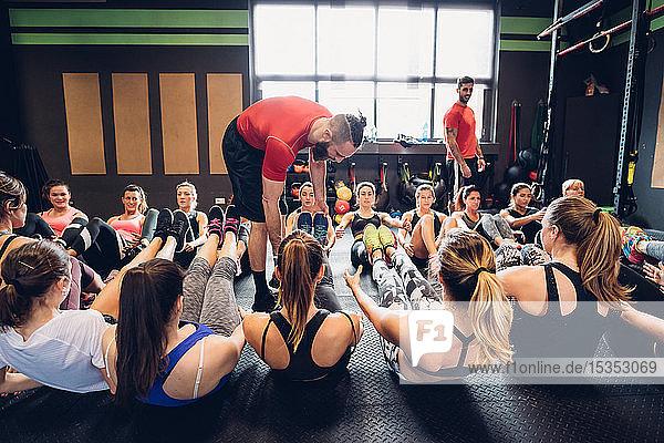 Frauen trainieren im Fitnessstudio mit männlichen Trainern  die mit angehobenen Beinen auf dem Boden sitzen