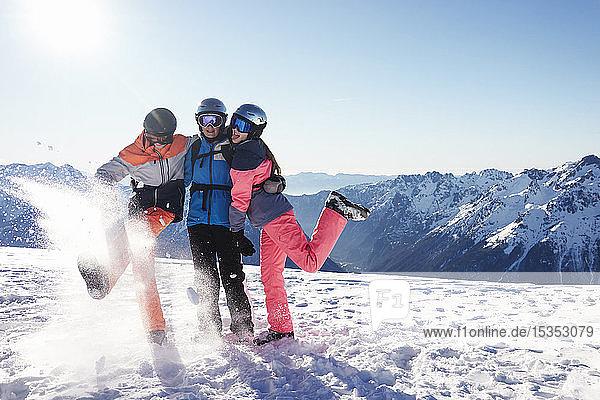 Skifahrer  Mutter mit jugendlichem Sohn und Tochter auf schneebedecktem Berggipfel  Alpe-d'Huez  Rhône-Alpes  Frankreich