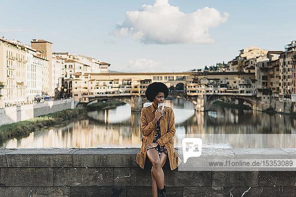 Junge Frau mit Afro-Haaren wartet auf der Brücke  Florenz  Toskana  Italien