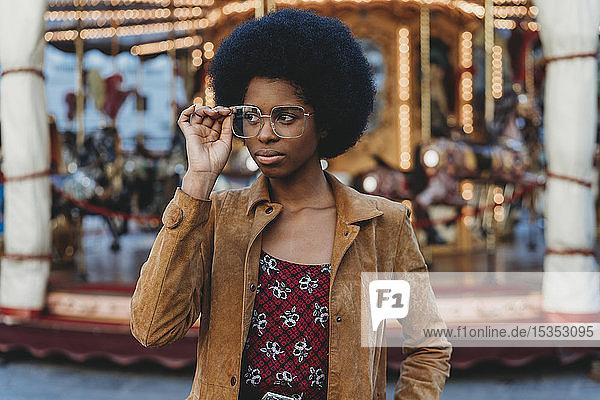 Junge Frau mit Afro-Haaren setzt vor dem Karussell eine Brille auf