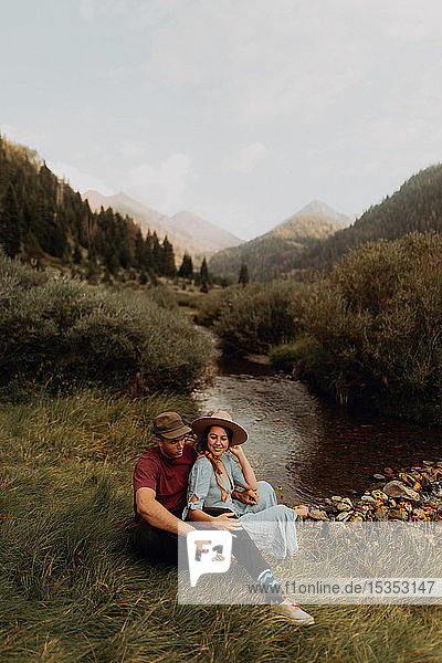 Young couple sitting by rural river  Mineral King  California  USA