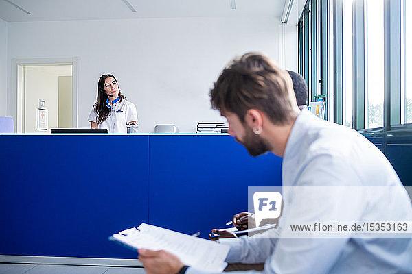 Krankenschwester spricht mit Patienten  die an der Krankenhausrezeption Formulare ausfüllen