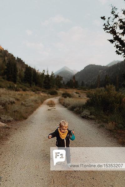 Female toddler toddling along rural road  Mineral King  California  USA