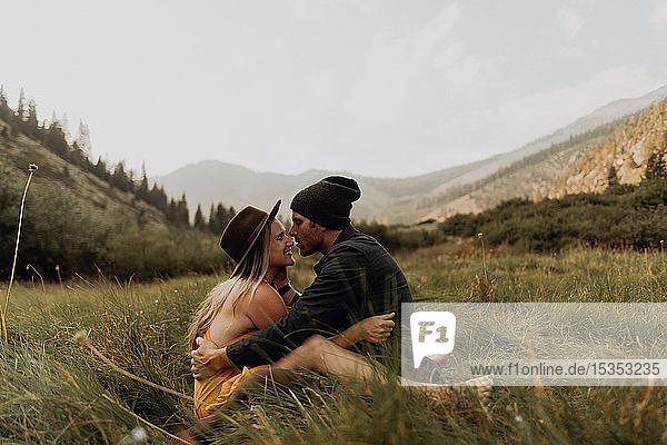 Mid adult couple sitting down hugging in rural valley  Mineral King  California  USA