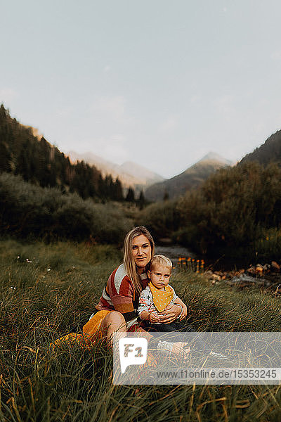 Female toddler sitting on mother's lap by rural river  portrait  Mineral King  California  USA