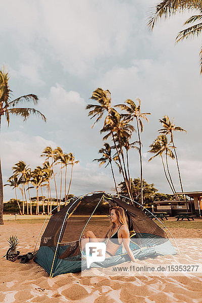 Woman in tent on sandy beach  Princeville  Hawaii  US