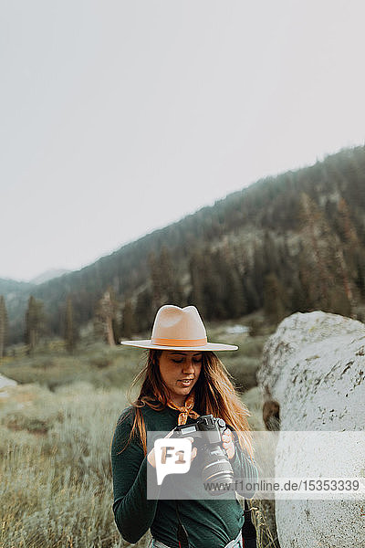Young woman in stetson reviewing photos on digital camera in rural valley  Mineral King  California  USA