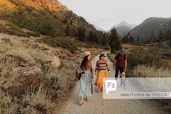 Weibliches Kleinkind mit Mutter und jungem Paar  die auf einer Landstraße watscheln  Mineral King  Kalifornien  USA