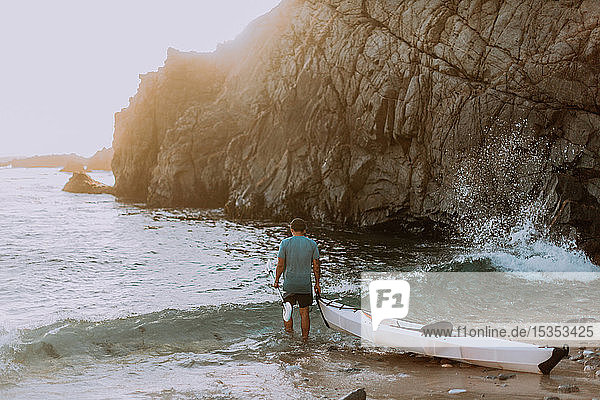 Man dragging kayak into sea  Big Sur  California  United States