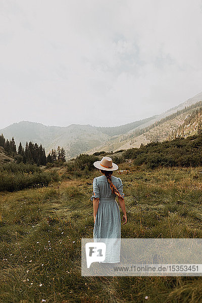 Young woman in stetson and maxi dress strolling in rural valley  rear view  Mineral King  California  USA