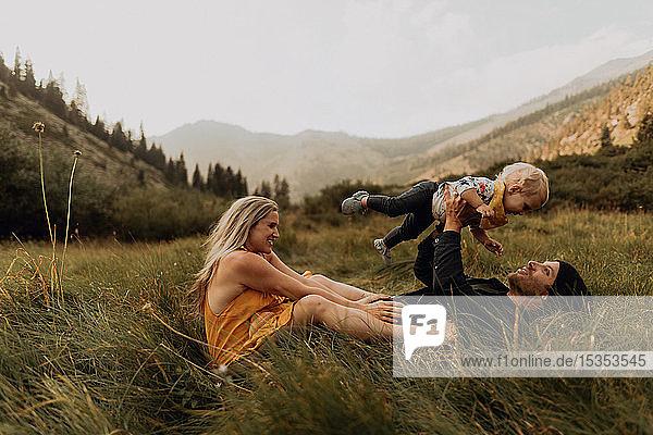 Mittelgroßes erwachsenes Paar hält Kleinkind-Tochter in ländlichem Tal hoch  Mineral King  Kalifornien  USA