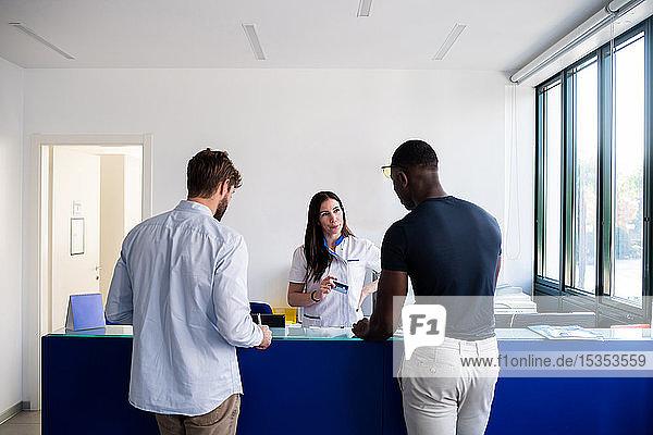 Krankenschwester im Gespräch mit Patienten am Krankenhausempfang